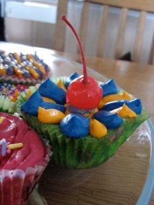 Muffins skreitt með smjörkremi (lituðu)og koktelberi